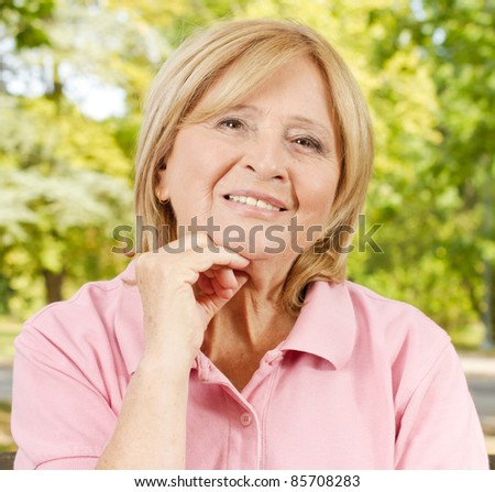 Closeup portrait of smiling senior woman in the park. - stock photo