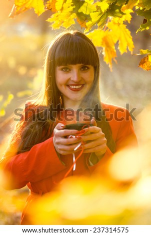 Closeup portrait of smiling woman holding hot of tea at autumn park - stock photo