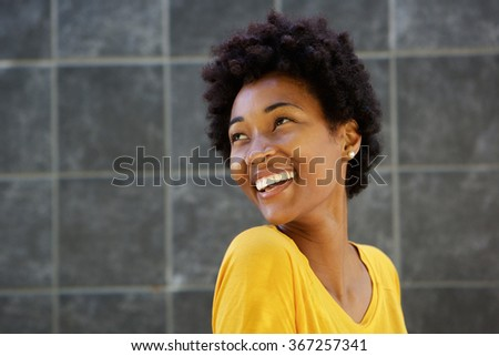 Closeup portrait of smiling young black woman looking over her shoulder against a gray wall