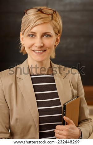 Closeup portrait of smiling young businesswoman looking at camera, holding folder in hand. - stock photo