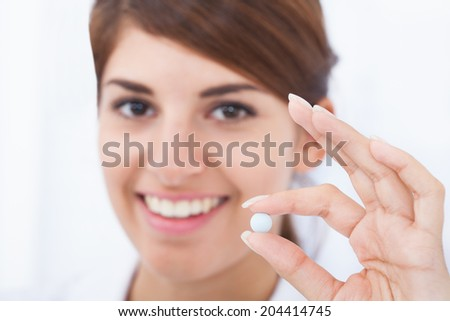 Closeup portrait of smiling young female doctor holding pill