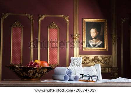 Closeup portrait of spectacles, yellow pencil, design drawing and white stucco moulding, on wooden table over classical interior at studio shot - stock photo