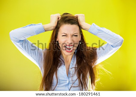 Closeup portrait of stressed business woman, pulling her hair out yelling screaming with temper tantrum isolated on yellow, green background. Negative human emotion facial expression reaction attitude - stock photo