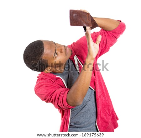 Closeup portrait of stressed, upset, sad, unhappy young man standing with, looking into empty wallet, isolated against white background. Financial difficulties, bad economy concept. Negative emotion