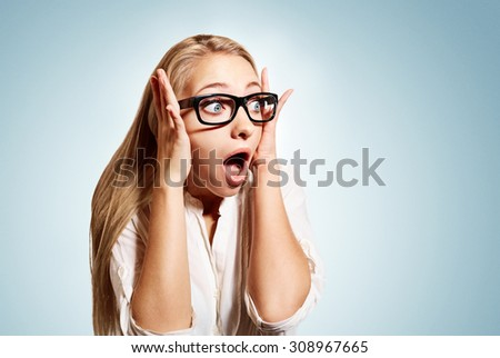 Closeup portrait of surprised young handsome blonde business woman looking shocked in full disbelief hands on head open eyes with glasses, isolated on blue background. Positive human emotion facial  - stock photo