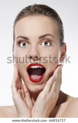 Closeup portrait of surprised young woman on white background