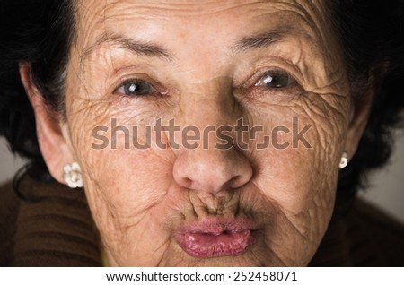 closeup portrait of sweet grandmother sending a kiss - stock photo