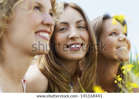 Closeup portrait of teenage girl smiling while friends looking away - stock photo