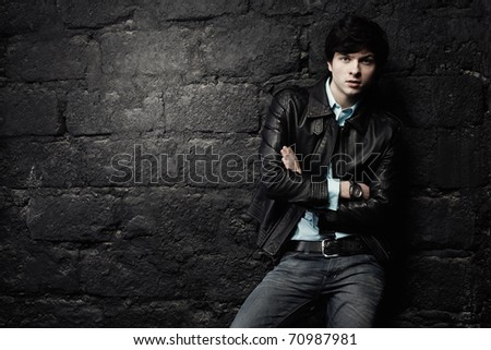 Closeup portrait of the beautiful young sexual man in a leather jacket, on a black background - stock photo