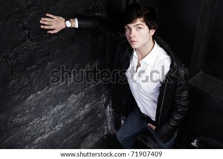 Closeup portrait of the beautiful young sexual man, on a black background - stock photo
