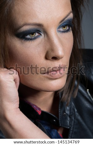 Closeup portrait of the face of a beautiful young woman with a worried expression staring thoughtfully into the distance - stock photo