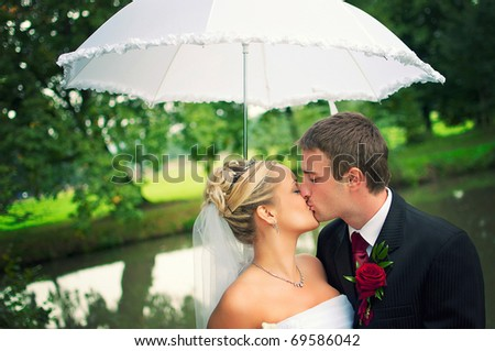 closeup portrait of the newlyweds kissing under a summer parasol - stock photo
