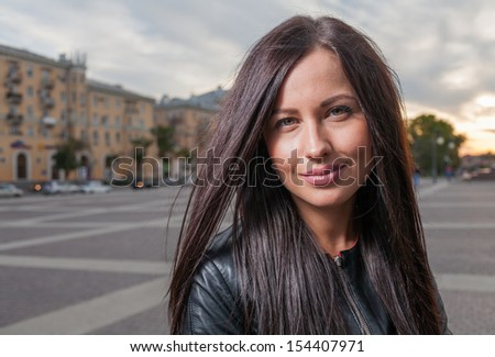 closeup portrait of the russian brunette 20s years old posing outdoors weared black leather jacket head and shoulders shot against night cityscape evening street view - stock photo