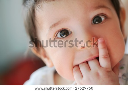 closeup portrait of the small boy with fingers in the mouth