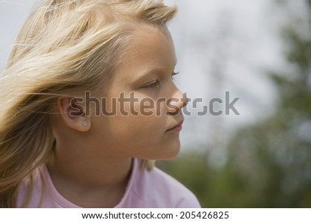 Closeup portrait of thoughtful looking young scandinavian girl outdoors on sunny summer day