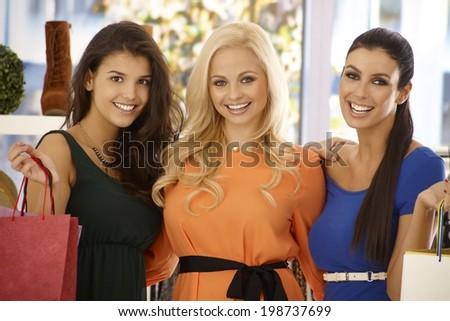 Closeup portrait of three beautiful shopping girls, smiling happy. - stock photo