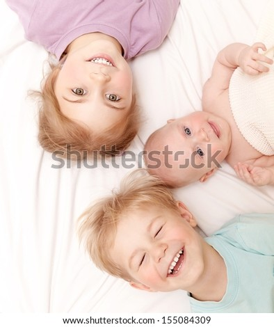 Closeup portrait of three cheerful kids lying down at home, newborn baby with brother and sister, happy family, love and friendship concept - stock photo