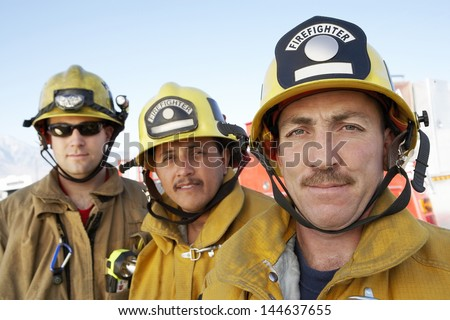 Closeup portrait of three fire fighters in helmets against sky - stock photo