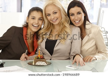 Closeup portrait of three happy businesswomen celebrating ones birthday at workplace with chocolate cake and candle. - stock photo