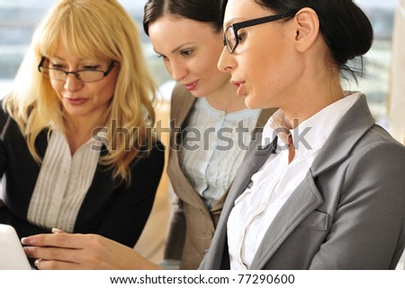 Closeup portrait of three women working indoor together with documents and laptop. - stock photo