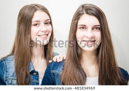Closeup portrait of two beautiful young women with long dark hair and natural makeup wearing jeans shirts happy smiling looking at camera