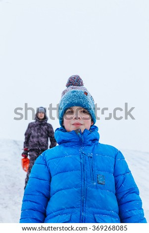 Closeup portrait of two boys, friends, standing on snowy hill. Winter holidays concept. - stock photo