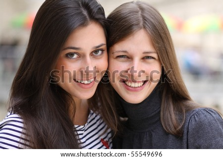 Closeup portrait of two happy pretty teenagers embracing