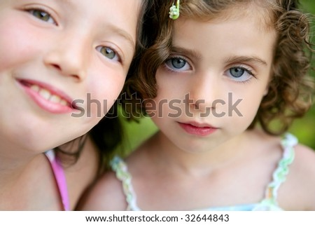 closeup portrait of two little happy beautiful girl sisters