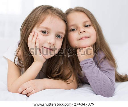 Closeup portrait of two little sisters - best friends - stock photo