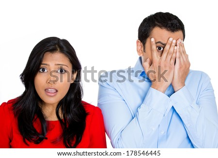 Closeup portrait of two people, man woman, can't believe what they see, one barely peeking through hand, isolated on white background. Negative emotion facial expression feelings.  - stock photo