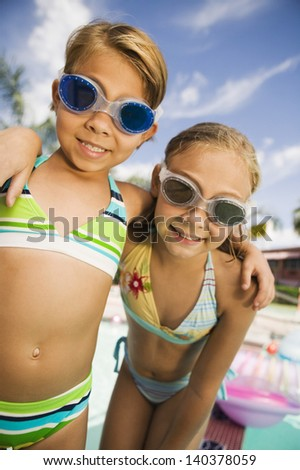 Closeup portrait of two smiling girls with arms around wearing swim goggles - stock photo