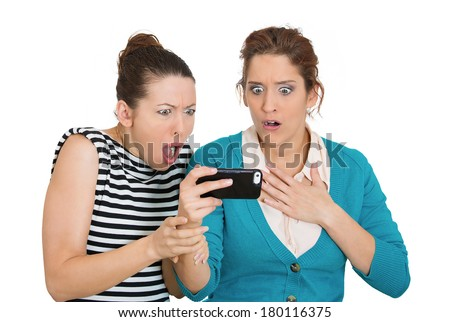 Closeup portrait of two women looking shocked upset while watching something on their cell phone, text message, ams, email isolated white background. Negative human emotions, facial expression feeling - stock photo