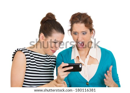 Closeup portrait of two women looking shocked upset while watching something on their cell phone, text message, mms, email isolated white background. Negative human emotions, facial expression feeling - stock photo