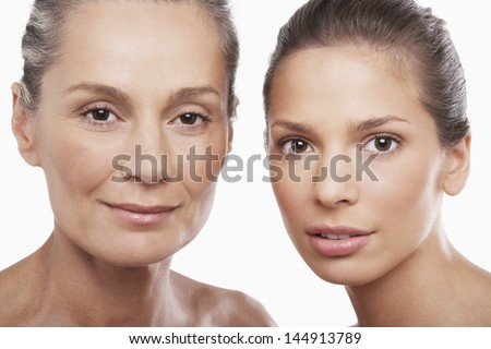 Closeup portrait of two women of different ages on white background - stock photo