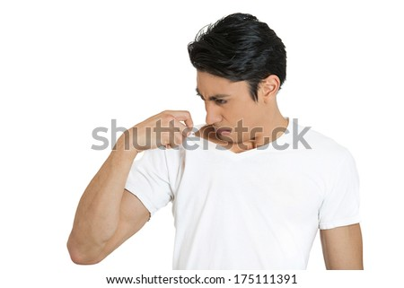Closeup portrait of unhappy young man, smelling, sniffing himself, something stinks, very bad, foul odor situation, isolated on white background. Negative human emotions, facial expressions, feelings