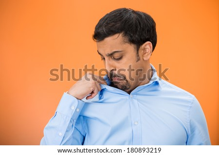 Closeup portrait of unhappy young man, smelling, sniffing himself, something stinks, very bad, foul odor situation, isolated on orange background. Negative human emotions, facial expressions, feelings - stock photo