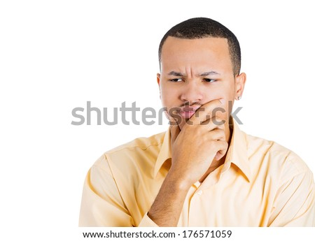 Closeup portrait of unhappy young man thinking daydreaming deeply bothered by something hand on face looking downwards, isolated on white background. Negative emotion facial expression feeling