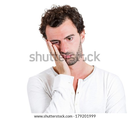 Closeup portrait of very sad depressed, stressed, alone, disappointed gloomy young man resting his face on hands, having suicidal thoughts isolated on white background. Human emotion facial expression