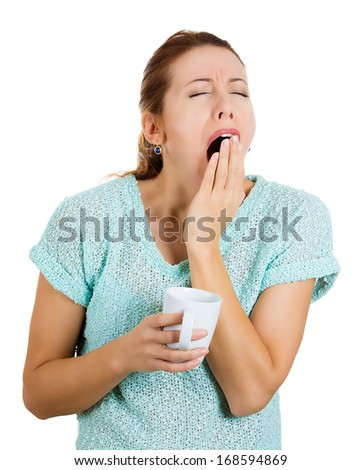 Closeup portrait of very tired, almost falling asleep businesswoman holding cup of coffee, struggling not to crash, stay awake, keep eyes opened, yawning, isolated on white background. Face expression - stock photo