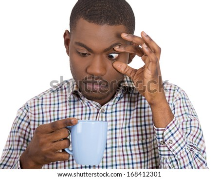 Closeup portrait of very tired, falling asleep young business man employee holding up a cup of coffee, struggling not to crash and stay awake, keeping his eyes opened, isolated on a white background  - stock photo