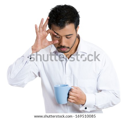 Closeup portrait of very tired falling asleep young student business man employee holding cup of coffee struggling not to crash and stay awake, keeping his eyes opened, isolated on a white background  - stock photo