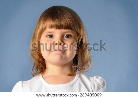 Closeup portrait of white two years girl looking directly at camera and making faces. She is blond and wear white t-shirt, standing on blue background at studio. - stock photo