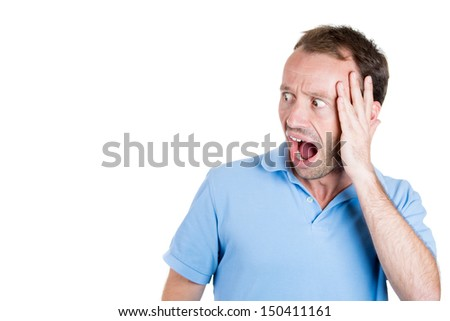Closeup portrait of wild, goofy, crazy, funny, shocked man's face looking to side with copy space, isolated on white background with copy space - stock photo