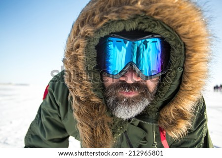 Closeup portrait of winter adventurer over sky and snow background. Active healthy sport lifestyle - stock photo