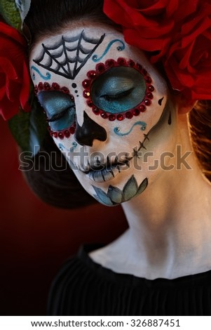 Closeup portrait of woman in santa muerte mask at halloween, eyes closed.