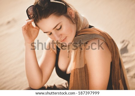 Closeup portrait of woman in sunglasses sitting on sand dune