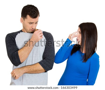 Closeup portrait of woman looking at man closing, cover nose, something stinks, very bad smell, odor. Guy sniffs himself.  Isolated on white background Negative emotion, facial expression, feeling - stock photo