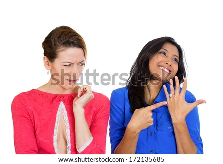 Closeup portrait of woman super excited to be engaged pointing to ring, and other lady looking very envious at her friend good fortune, isolated on white background. Negative emotion facial expression - stock photo