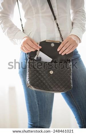 Closeup portrait of woman taking keys out of purse - stock photo
