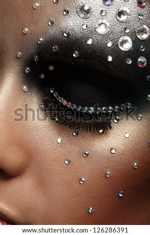 Closeup portrait of woman with artistic make-up - stock photo